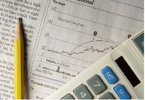 Newspaper stock chart with calculator and pencil