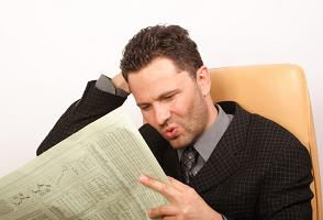 man reading poor financial results in newspaper